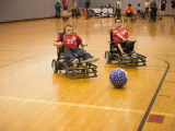 Two college males in Powersoccer wheelchairs racing after a soccerball.