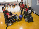Three young adult males in red jerseys, sitting in powersoccer wheelchairs are having a conversation with their coach while a soccer ball sits between them.