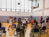 Eight college students are playing an unorganized game of basketball. The students are using sports wheelchairs and are surrounded by community members and a few individuals seeming to act as coaches.