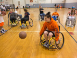 Six college students, and one young boy rolling around in sports wheelchairs. Ons of the students, a female, is chasing a basketball. There is also a male onlooker holding a basketball to the side, conversing with one of the players in a wheelchair.