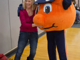 An adult female is hugging Otto in front of a MoveAlong banner.