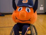 Otto the Orange in a sports wheelchair with both hands up in the air.