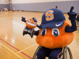 Otto the Orange in a sports wheelchair with one hand up in the air and the other holding a stuffed Otto the Orange in a wheelchair.