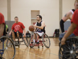 Five male, college students, playing wheelchair basketball. three are wearing red team shirts and two are wearing black jerseys. One of the males in the black jersey is holding the basketball and about to pass it to a teamate.