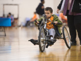 A young male is rolling across the floor in a handcycle. His mother is following behind him.