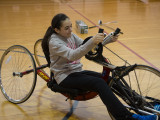 A college female rolling around in a handcycle.