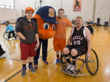 Two young boys, Otto and an adult male in a sports wheelchair are linking arms and facing towards the camera.
