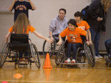Four individuals in sports wheelchairs participating in a relay. Two contestants are slapping hands as the second contestant begins her leg of the race.