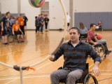 A young male is a sports wheelchair is shooting a ball into a quiddich hoop. In the backgroud are many other people with different sports balls rolling around the court.