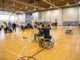 Two college aged boys playing quidditch in sport wheel chairs at OrangeAbility. Ball is in the air headed towards the net, while one boy tries to block the shot.