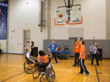 A Syracuse University advisor and a male athlete playing basketball while using sports wheelchairs. There are 3 college males and one college female watching the shot move towards the hoop.
