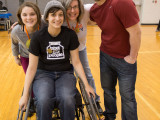 Three college students and a faculty member linking arms and smiling for the camera. One of the students is situated towards the front and is sitting in a sports wheelchair.