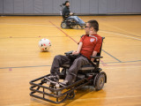 Two college male students playing power soccer. The student in the background appears to be passing the ball to the student in the front of the frame. Both students are using power soccer chairs