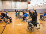 10 individuals, made up of college students, MoveAlong board members, and community members participating in a game of wheelchair basketballs. The individual in the foreground of the photo is passing the basketball to a teamate situated further back.