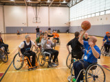 12 individuals, including college students, MoveAlong board members and other various community participants participating in wheelchair basketball. One of the MoveAlong members is about to pass the basketball to his right.