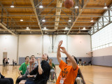 A Syraucse University student making a basketball shot, while playing a game of wheelchair basketball. He is surrounded by 5 other teamates and opponents.