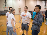 Four volunteers at OrangAbility having a conversation. Three of the Volunteers are wearing 2013 OrangeAbility tee-shirts