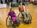 A young girl and a women are sitting next to each other in sports wheelchairs. The woman is leaning into the young girl and pointing into something that is not seen in the frame.