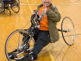 A college boy using a handcycle, smiling towards the camera and giving a thumbs-up!