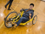 A college male, wearing a fraternity sweatshirt using a handcycle at OrangeAbility.