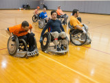 Six males using rugby wheelchairs rolling towards the left side of a basketball court. The object they are rolling towards is not seen in the photo.