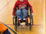 A young boy rolling around in a sports wheelchair.