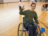 A college aged male sitting in a sports wheelchair and waving towards the camera. In the background is a basketball court with some cones, and other participants wheeling around.