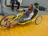 A college female using a yellow handcycle and smiling at somebody not in the photo.