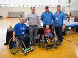 Four adult males and a young boy smiling in front of the MoveAlong table. One of the adults and the young boy are in sports wheelchairs.