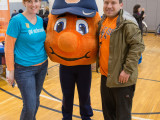A college male and a female staff member linking arms with Otto the Orange and smiling towards the camera.