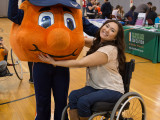 A young female in a wheelchair hugging Otto the Orange. Otto has his arm up in the air.