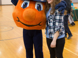 A college female standing next to Otto the Orange. Otto has one arm hugging the girl and the other up in the air.