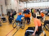 Seven college students playing wheelchair basketball with Otto the Orange. Otto is holding the basketball and looks like he is about to take a shot. There is a group of seven or eight onlookers in the background.