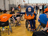 Five college students and Otto playing basketball in sport wheelchairs. Otto is high-fiving a student while a group of onlookers take pictures.