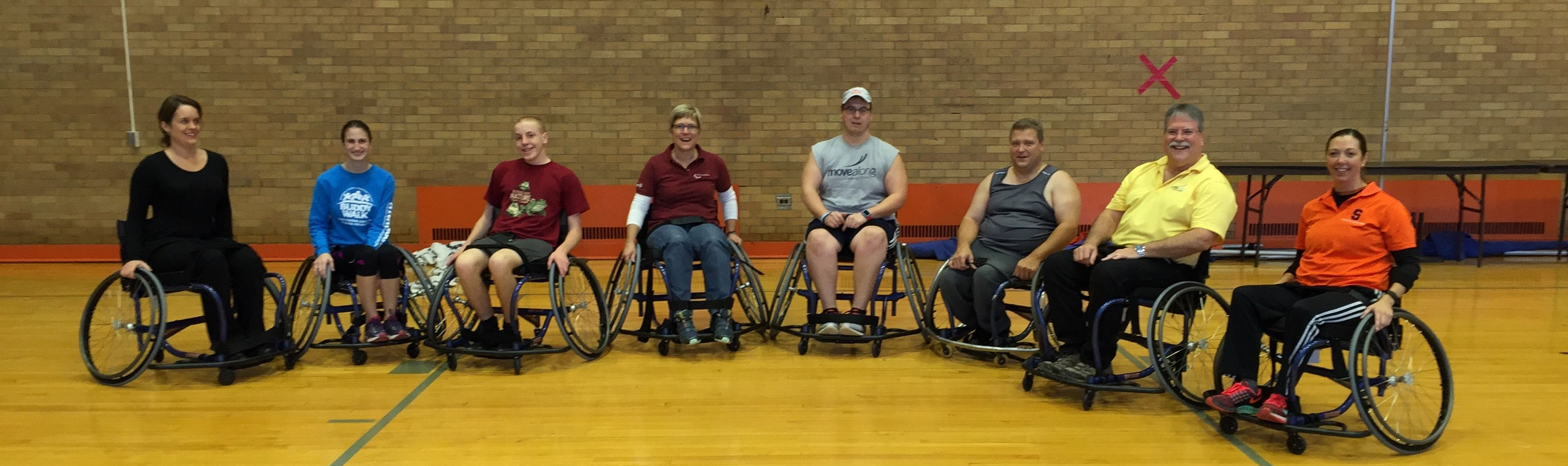 A group of 8 players made up of students, faculty, staff, alumni, and community members sit in a semi-circle after playing wheelchair basketball